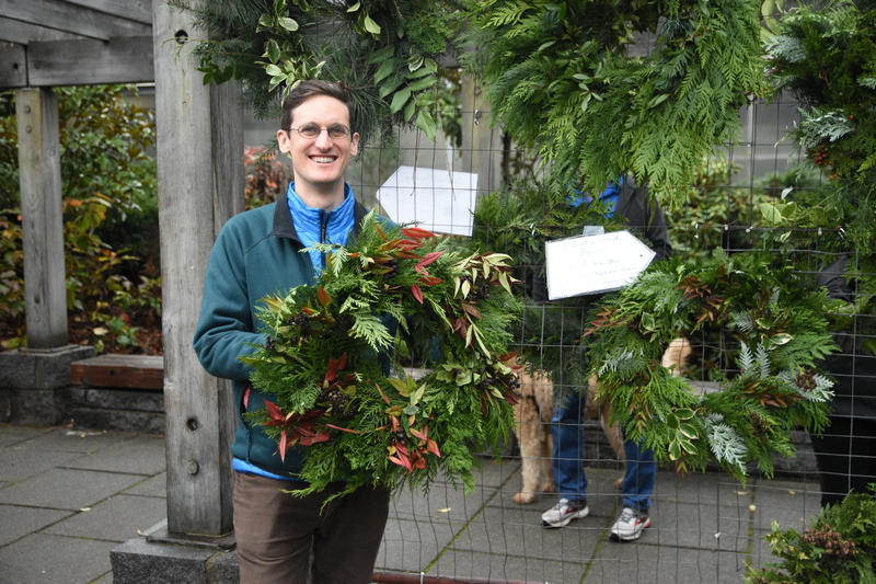 Holiday shopper getting a handmade wreath from the Arboretum Foundation