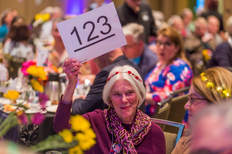 woman at dinner table holding up auction bid card